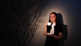 A woman in an elegant dress drinking coffee in a dark room. Sensual female with hair style holding a cup of coffee in. A woman in an elegant dress drinking stock footage