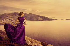 Woman in Elegant Dress on Mountain Coast, Fashion Model Gown. Woman in Elegant Dress on Mountain Coast, Fashion Model in Flowing Gown Cloth, Looking to Landscape Stock Photography