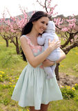 Woman in elegant dress posing with her baby boy in blossom garde. Fashion outfoor photo of gorgeous woman with dark hair in elegant dress posing with her baby Stock Images