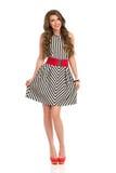 Woman In Elegant Striped Dress. Smiling beautiful woman in black and white striped dress and high heels. Full length studio shot isolated on white Stock Photography
