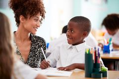 Free Woman Elementary School Teacher Giving Male Pupil Wearing Uniform One To One Support In Classroom Royalty Free Stock Photography - 153633237