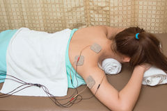 Woman with eletrical stimulator for increase muscle strength Stock Photos
