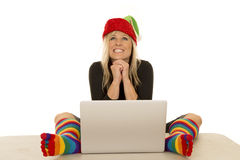 Woman elf with colorful socks around laptop look up smile Stock Photography