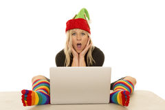 Woman elf with colorful socks around laptop shocked Royalty Free Stock Images
