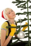 Woman elf in yellow gloves and red cap decorating green fir isol stock photos