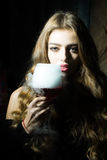 Woman with elixir of beauty. Closeup view portrait of one beautiful young sensual serious enigmatic enchanted woman holding in hand drinking glass full of liquid stock images