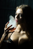 Woman with elixir of beauty. Closeup view portrait of one beautiful young sensual serious enigmatic enchanted woman holding in hand drinking glass full of liquid royalty free stock photos