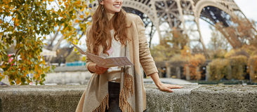 Woman on embankment in Paris holding map and looking aside Royalty Free Stock Image