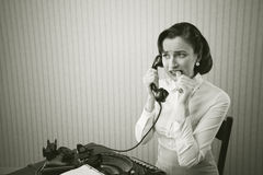 Woman talking on phone at desk royalty free stock photos