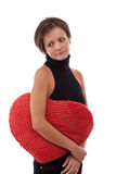 Woman embrace a heart-shape pillow Royalty Free Stock Image