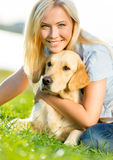 Woman embraces golden retriever on the grass Royalty Free Stock Images
