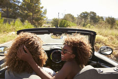 Woman embraces her partner as he drives, rear passenger POV Royalty Free Stock Photos
