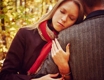 Woman embraces a man in autumn park Royalty Free Stock Images