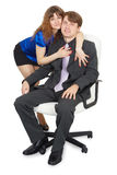 Woman embraces a young man in an office chair Royalty Free Stock Photos