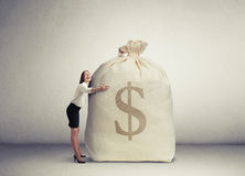 Woman embracing big bag with money Stock Image