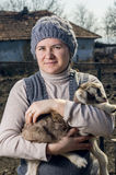 Woman embracing a goatling. Stock Photos