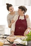 Woman embracing her grandma. While cooking together Stock Photo