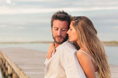 Woman embracing her man from behind at seaside Royalty Free Stock Images