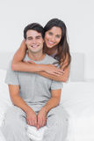 Woman embracing her partner sat in bed Stock Photos