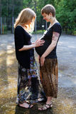 Woman embracing her pregnant friend's belly Stock Photos