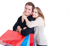Woman embracing his man holding bunch of shopping bags Royalty Free Stock Photos