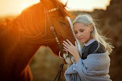 Woman embracing horse head in nature stock images