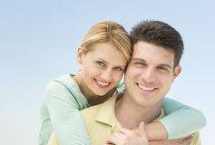 Woman Embracing Man From Behind Against Clear Blue Sky Stock Photo