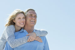 Woman Embracing Man From Behind While Looking Away Against Sky. Low angle view of happy mature women embracing men from behind while looking away against clear Royalty Free Stock Photo
