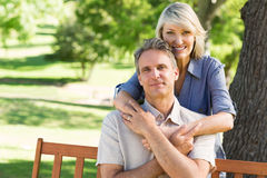 Woman embracing man from behind in park Royalty Free Stock Images