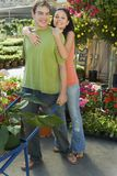 Woman Embracing Man At Botanical Garden. Portrait of a happy young women embracing men from behind at botanical garden stock photo