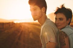 Woman embracing a man outdoors on a road trip. Woman embracing a men from behind on a mud track highway in countryside. Romantic couple on the highway spending Stock Photography