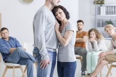 Woman embracing man during therapy Stock Images