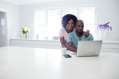 Woman embracing man while using laptop Stock Images