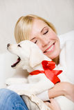 Woman embracing puppy with red ribbon Royalty Free Stock Photos