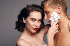 Woman embracing and shaving man. Young women looking at camera and shaving handsome men while embracing him. Horizontal studio shot royalty free stock photos