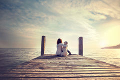 Woman embracing sweetly his dog while looking the view Royalty Free Stock Photography