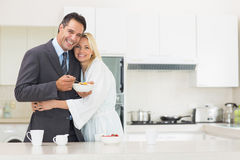Woman embracing well dressed man in the kitchen Royalty Free Stock Images