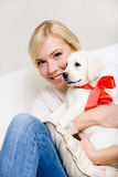 Woman embracing white puppy with red ribbon Stock Photography
