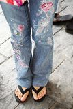 Woman in embroidered jeans and sandles stock images