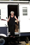 Woman emerging from trailer. Smiling woman stepping down  from a luxury camping trailer Royalty Free Stock Images