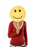 Woman with emoticon. Young adult woman holding smiley emoticon on white background. Vertical shape, front view, waist up Royalty Free Stock Photos