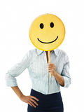 Woman with emoticon. Young adult woman holding smiley emoticon on white background. Vertical shape, front view, waist up Stock Image