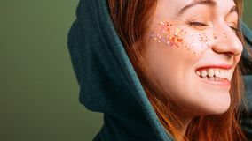 Woman emotion smiling eyes closed glitter freckles. Woman emotion. Happy young female smiling with eyes closed. Glitter freckles makeup. Copy space on green stock photo