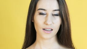 Woman with emotion of patience bites lip on yellow background. Slowly stock video footage