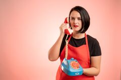 Free Woman Employed At Supermarket With Red Apron And Black T-shirt Talking On An Old Phone Stock Photography - 191581662