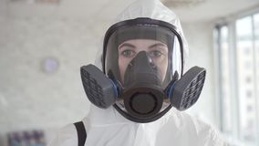 A woman employee of a cleaning service or the exterminator posing at the camera