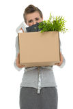 Woman employee hiding behind box with items. Fired woman employee hiding behind box with personal items Royalty Free Stock Images