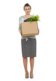 Woman employee holding box with personal items. Concerned woman employee holding box with personal items Stock Photo