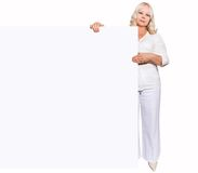 Woman with empty board - 50 years old Stock Image