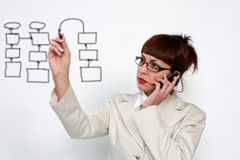 Woman with an empty diagram. Business woman is writing a diagram on the glass board while talking on the mobile phone Stock Photo